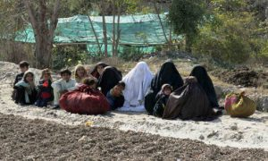 Women and children sit on by a road, while fleeing from a military offensive against the Pakistani Taliban, on the outskirts of Bannu located in Khyber Pakhtunkhwa province