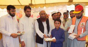 Office-bearers of the Al-Khidmat Foundation giving away gifts and cash amount to an orphan. - Sajif Ali Kokikhel